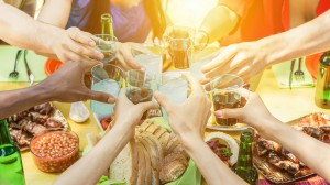 Group of friends toasting with aperitif eating barbecue outdoor - Closeup of hands cheering with cocktails and beers - Friendship,summer,fun and dinner concept - Soft focus on right bottom hand