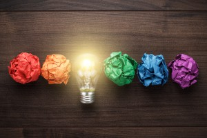 great idea concept with crumpled colorful paper and light bulb on wooden table